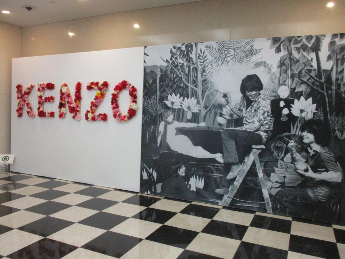 花で彩られたKENZOの文字と、若き日の高田賢三が最初の店の壁画を描いている巨大なモノクロ写真