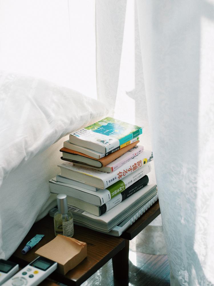 伊藤紺さんの自宅のベッドサイドに積まれた本